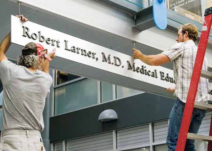 Workers install new signage in the Given Courtyard last year as the educational facilities at the College of Medcine were renamed in honor of Robert Larner, M.D.'42.