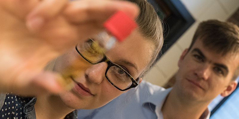 UVM doctoral student Morgan Cousins holds up unusual dye containing Boron. --Photo courtesy of Joshua Brown