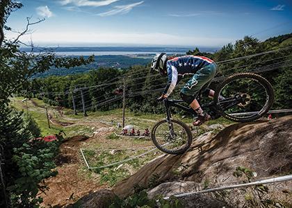Mazie hayden on a bike heading down a steep rock outcrop on a ski slope