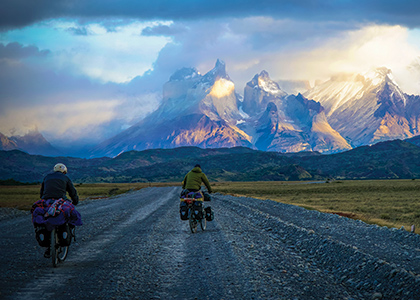 Cameron Russell and companion bicycling toward the a mountain range in Chile