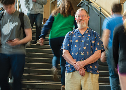 Pat Brown standing on the main staircase of the Davis Center with students streaming around him