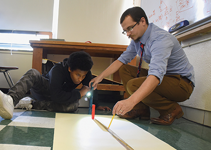 High School teacher Tom Payeur on teh floor with a student mapping something out on a sheet of paper.