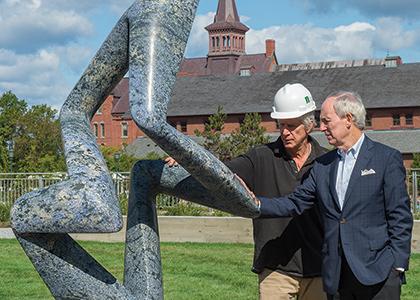 "President Sullivan with sculptor  Richard Erdman at the recent  installation of ""Areté Blu."""