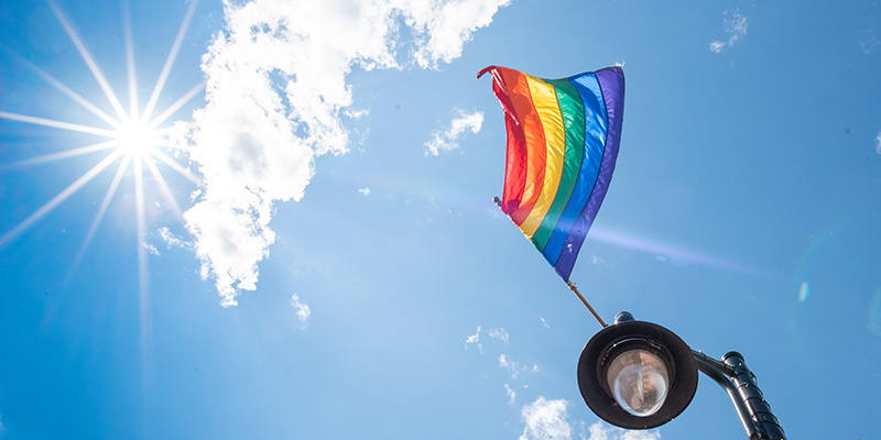 Rainbow pride flag flies off of lampost against blue sky with bright sun