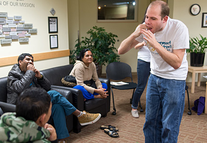 Class of 2016 medical student Ben Earle demonstrates flossing during a session on oral health at the Community Health Center of Burlington, as a group of refugees from Bhutan try it out. Earle co-organizes the Refugee Healthcare Orientation Student Interest Group. (Photo by Raj Chawla)