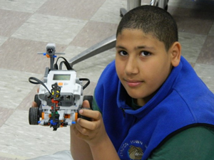 Boy proudly holding his completed robot