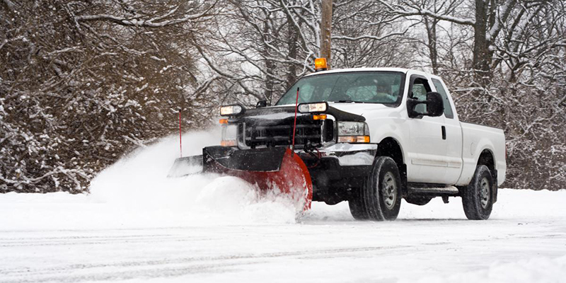 white pickup truck plowing snow