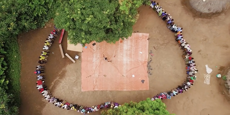 An aerial view of villagers standing in a circle