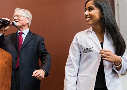 Dean Rick Morin, M.D., gives third-year medical student  Soraiya Thura the first  Larner College of Medicine white coat.
