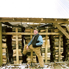 Don stands next to the 10-12 cords of firewood he burned each year at the Research Forest.