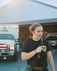Young woman in EMT uniform in front of a UVM ambulance