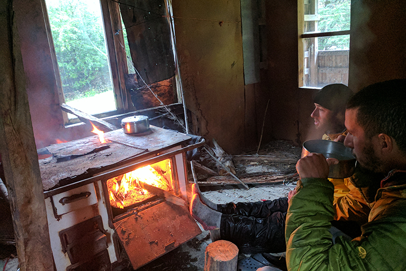 two guys warming their feet at a wood stove in a cabin