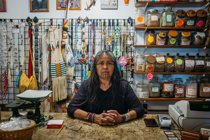 A native American woman stands behind the register at a gift shop.