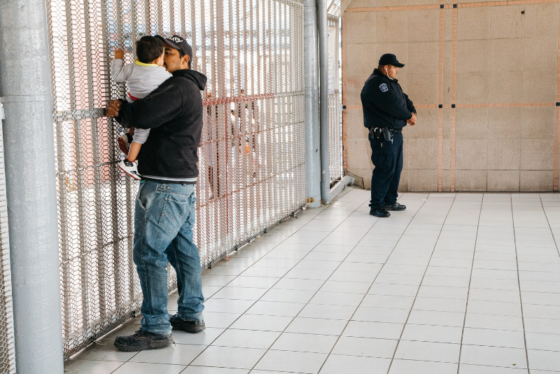 A man holding his son while they wait at a gate at the United States Customs office.