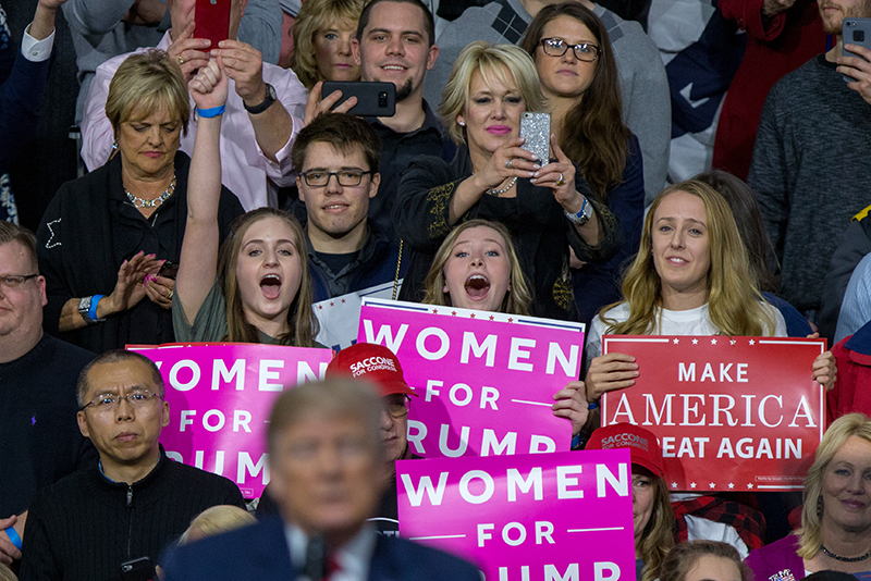 Crowd of Trump supporters at a rally hold signs
