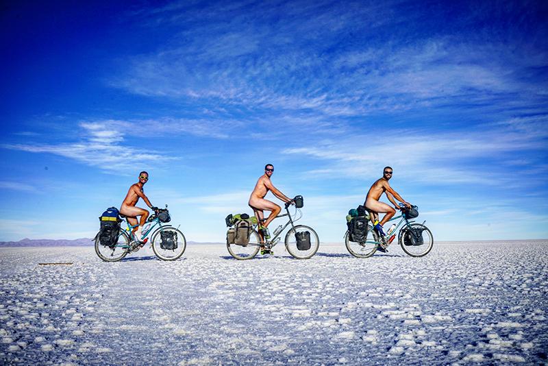 3 naked boys on bikes in the desert