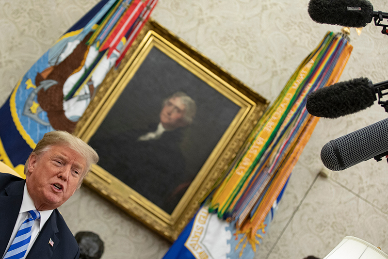 Trump sits in Oval Office under microphones