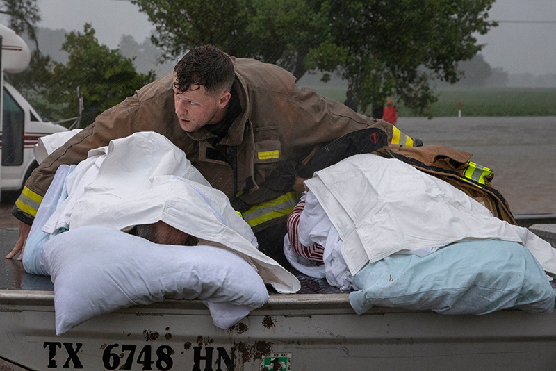 Firefighter holds two patients in hurricane floodwaters