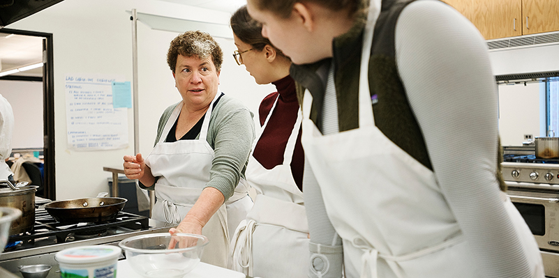 woman teaching students in kitchen lab