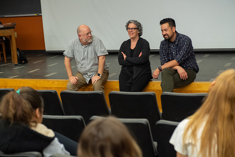 Professors Paul Besaw, Vicki Brennan and Jom Hammack address students in a lecture hall.