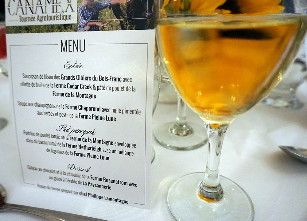 a glass of wine on a table next to a menu that showcases local foods