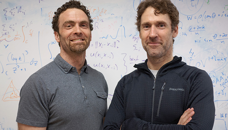 Chris Danforth and Peter Dodds standing in front of a white board covered in mathematical notations.