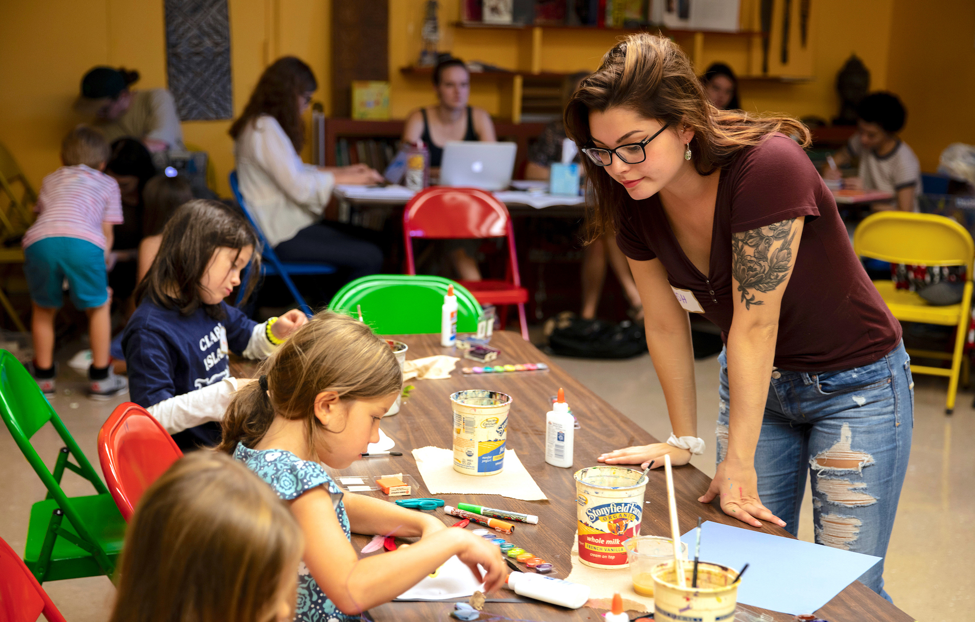 UVM Junior Ashley Bertolino instructs young artists in making masks during Erika White's Art Education class in the Fleming Museum's education workshop.