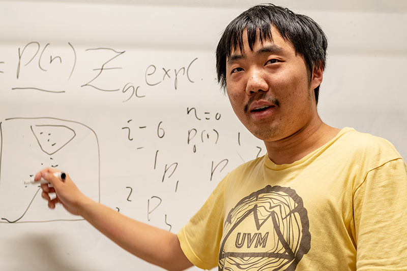 University of Vermont student Jiangyong Yu in front of white board