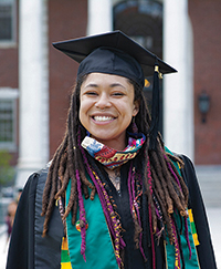 Smiling Kia Hanron in cap and gown in front of Waterman Building.