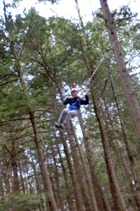 Student on the UVM Adventure Ropes Course after evaluating trees within and surrounding the course.