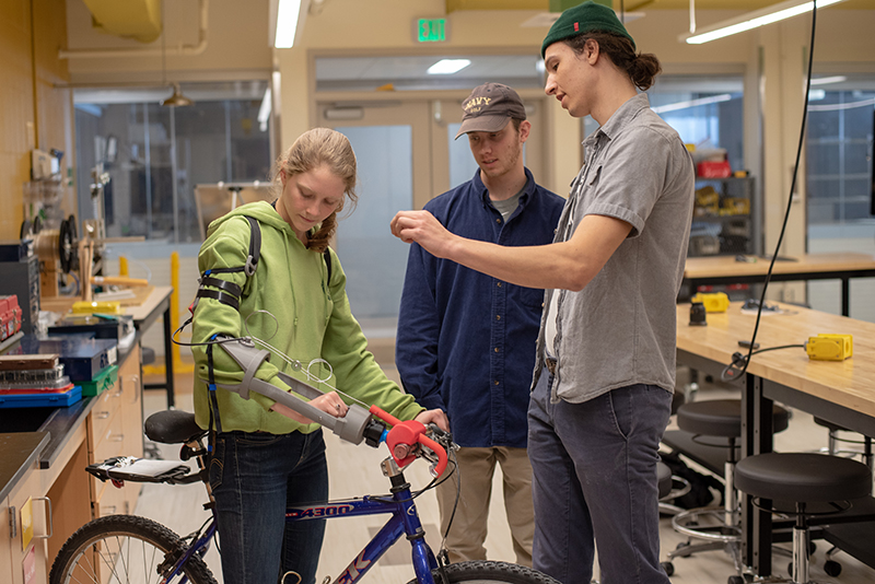 Three University of Vermont students stand around a bike outfitted with a prosthetic arm