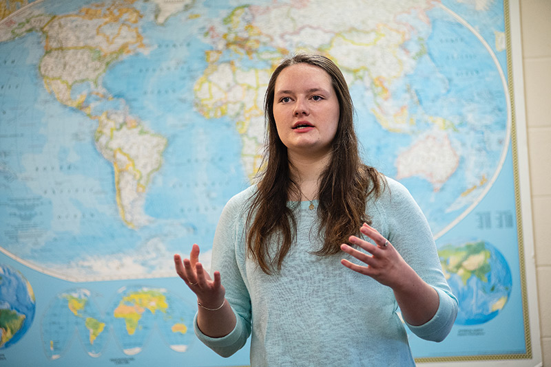 Hayley Barriere in front of a world map in the office of international studies