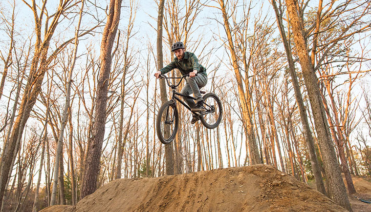 Biker riding off a dirt hill in the woods