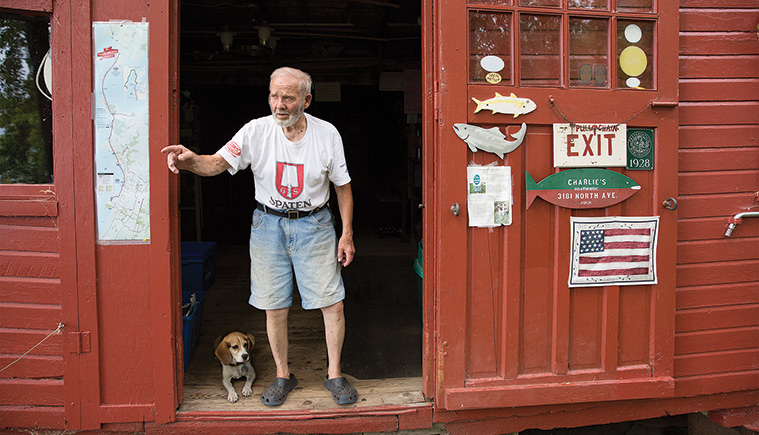 Charlie Auer and his hound dog in the doorway of Auer's Boathouse