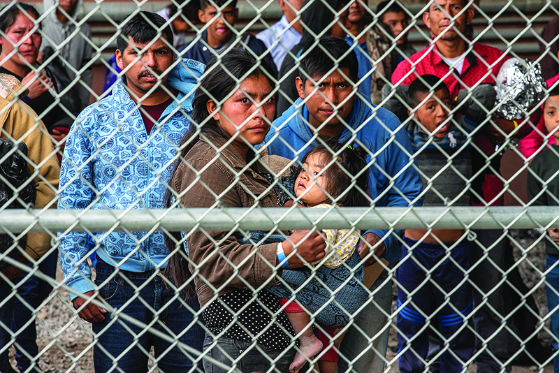 people waiting behind a chain link fence at the southern U.S.  Mexico border
