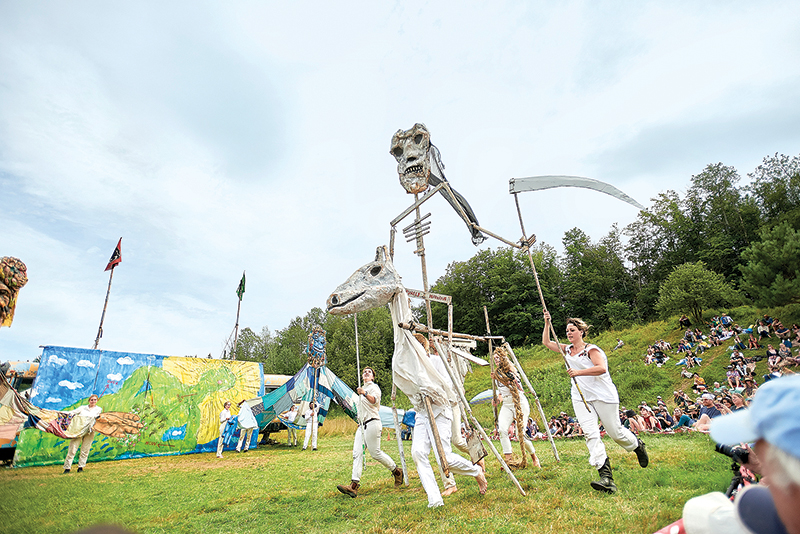 Open field with performers running around carrying tall puppets at the Bread and puppet circus outdoor theater.