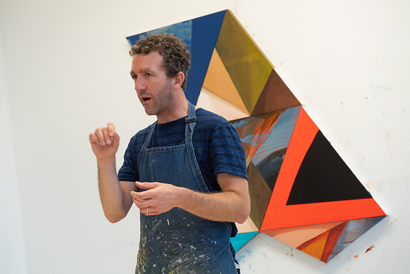 Artist Steve Budington talks in his studio in front of large painting