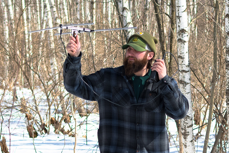 Chris Lampart holds radio device in winter woods