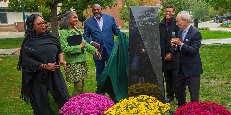 Staff alumni and students stand around a marker reading Andrew Harris Commons