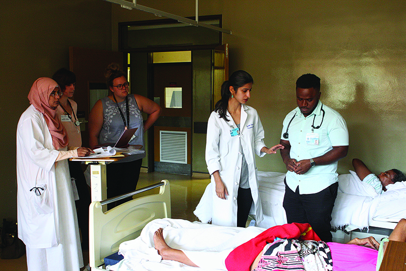 nurses, doctors, med students gathered around a hospital bed in an ICEC clinic.
