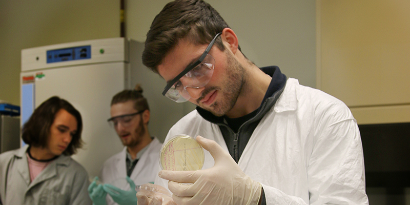 James in white coat and goggles working on a petrie dish in a lab