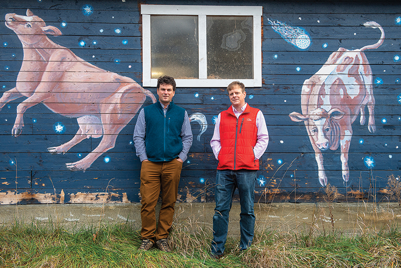 Andy and Mario Kehler standing in front of a barn painted with cows in outer space