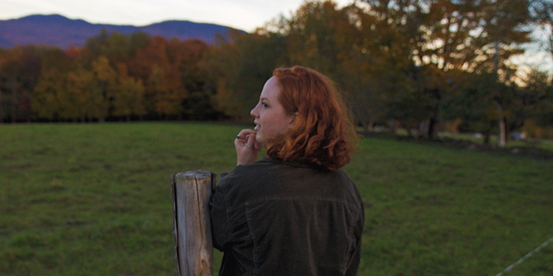 UVM student Jill Williamson stands in a field in autumn with her back toward camera
