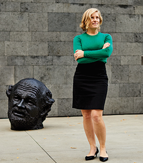 Kate Sylvester in front of a sculpture of a head lying on the ground at the San Francisco Museum of Modern Art