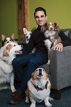 David Lipschultz sitting surrounded by dogs on floor and on his lap.