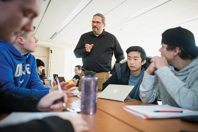Eric Monsen teaching a business seminar with students around a table.