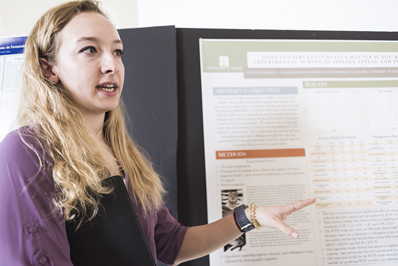 Student stands in front of presentation