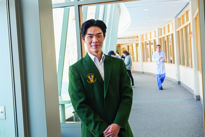 Nursing student Ken Nguyen standing in the hallway outside the medical library, wearing a UVM green Bolder Society jacket.