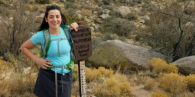 Olivia leaning against a trail marker for Sandia Mountain Wilderness