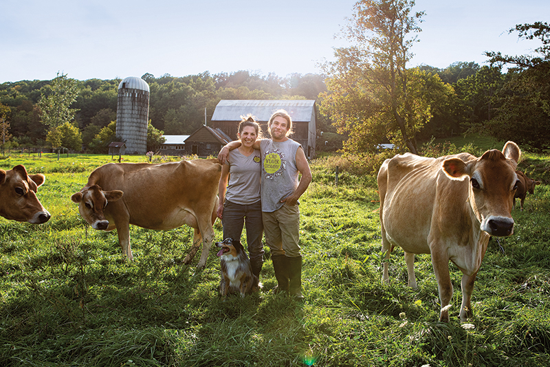 Kate Turcotte and her husband standing in a sunlit field with their cows.